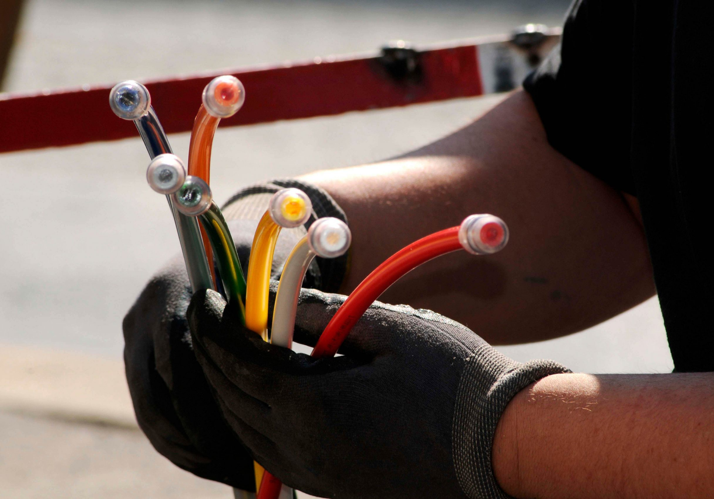 technician with multicolored fiber optic cables for high speed broadband internet